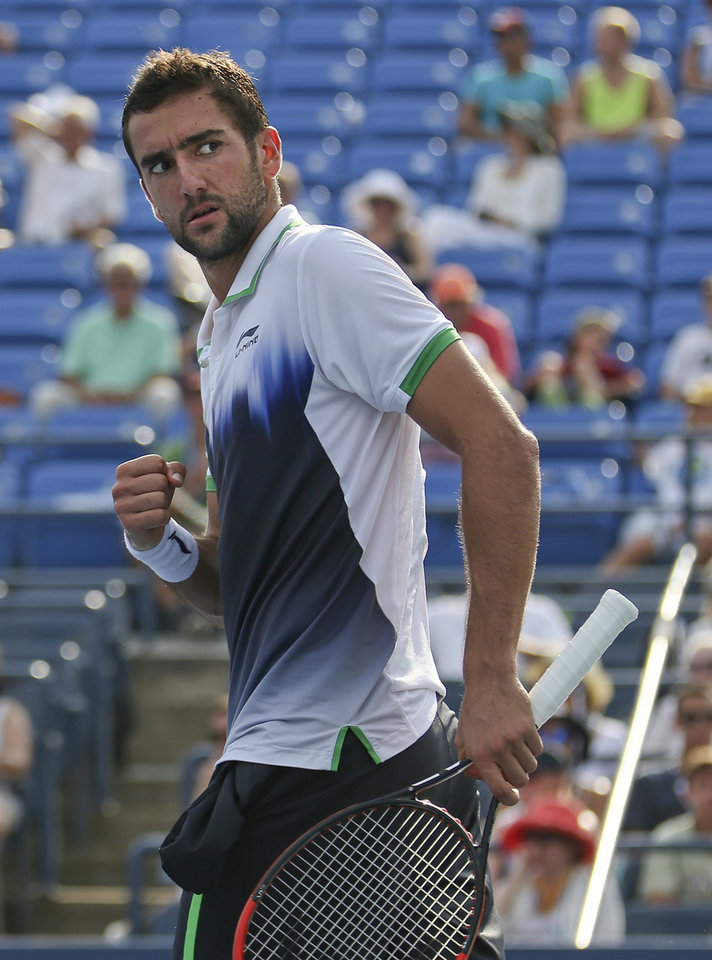 Photo - Gilles Simon, of France, reacts after a shot to Marin Cilic, of Croatia, during the fourth round of the 2014 U.S. Open tennis tournament, Tuesday, Sept. 2, 2014, in New York. (AP Photo/John Minchillo)