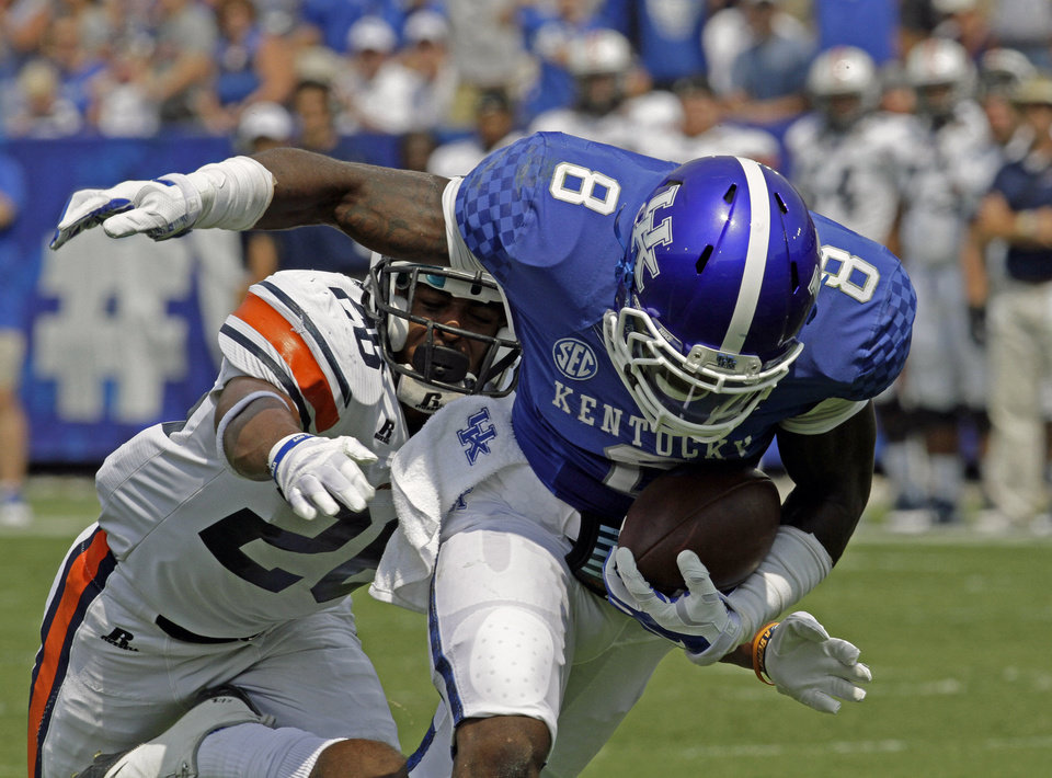 Photo - Kentucky wide receiver Javess Blue (8) maintains his balance after grabbing a pass in front of Tennessee-Martin safety Walter Evans (26) in the first half of an NCAA college football game in Lexington, Ky., Saturday, Aug. 30, 2014. (AP Photo/Garry Jones)
