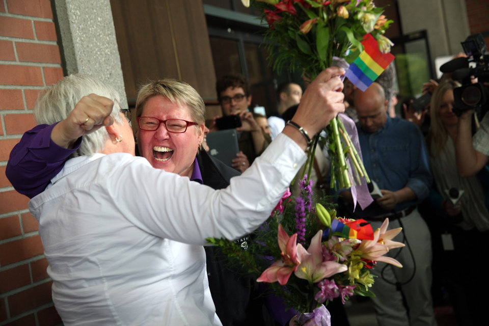 Photo - Deanna Geiger, left, and Janine Nelson, her partner of 32 years, react to news that they can get their Oregon marriage license, Monday, May 19, 2014, in Portland, Ore., following a federal judge's ruling the ban of same-sex marriage unconstitutional.  (AP Photo/The Oregonian, Faith Cathcart)  MAGS OUT; TV OUT; LOCAL TV OUT; LOCAL INTERNET OUT; THE MERCURY OUT; WILLAMETTE WEEK OUT; PAMPLIN MEDIA GROUP OUT.