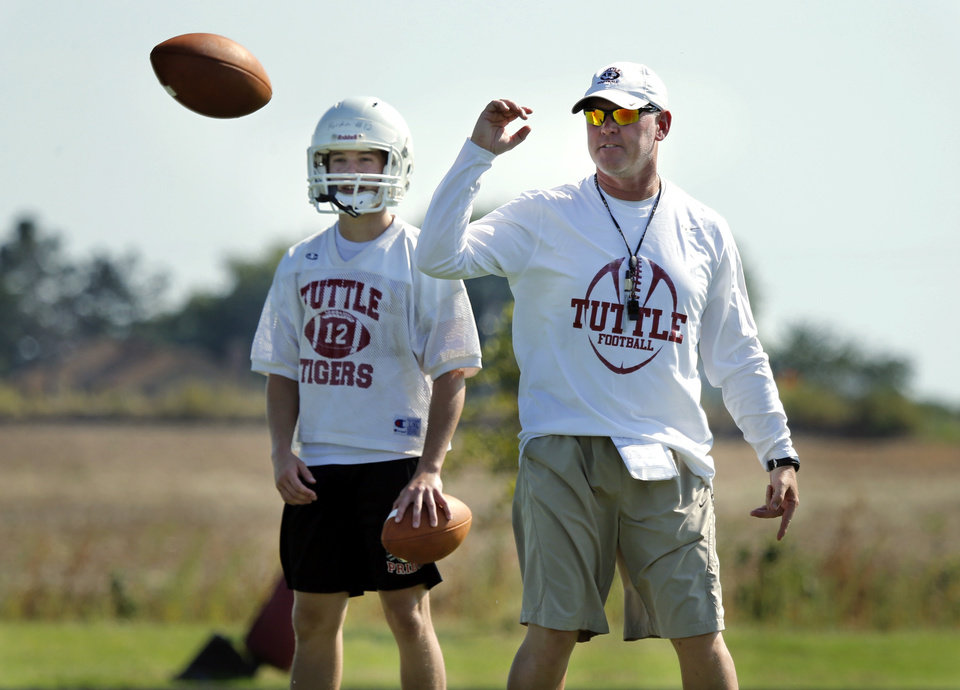 Photo - New head coach Brad Ballard works with quarterbacks during high school football practice on Tuesday, Aug. 12, 2014 in Tuttle, Okla. Photo by Steve Sisney, The Oklahoman
