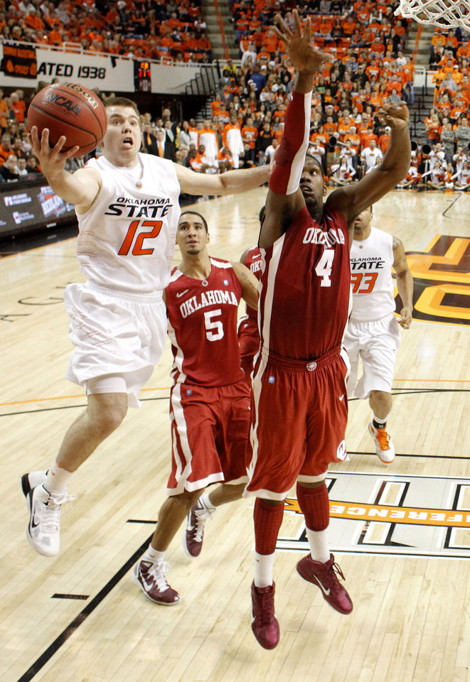 Photo - Oklahoma State's Keiton Page (12) goes past Oklahoma's C.J. Washington (5) and Andrew Fitzgerald (4) during the Bedlam men's college basketball game between the University of Oklahoma Sooners and Oklahoma State University Cowboys at Gallagher-Iba Arena in Stillwater, Okla., Saturday, February, 5, 2011. Photo by Bryan Terry, The Oklahoman