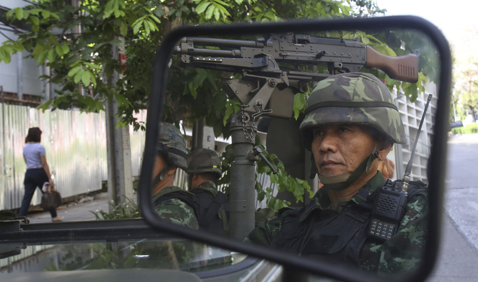 Photo - Thai soldiers are reflected in a mirror while guarding the Thai police headquarters Tuesday, May 20, 2014, in Bangkok, Thailand. Thailand's army declared martial law before dawn Tuesday in a surprise announcement it said was aimed at keeping the country stable after six months of sometimes violent political unrest. The military, however, denied a coup d'etat was underway. (AP Photo/Sakchai Lalit)