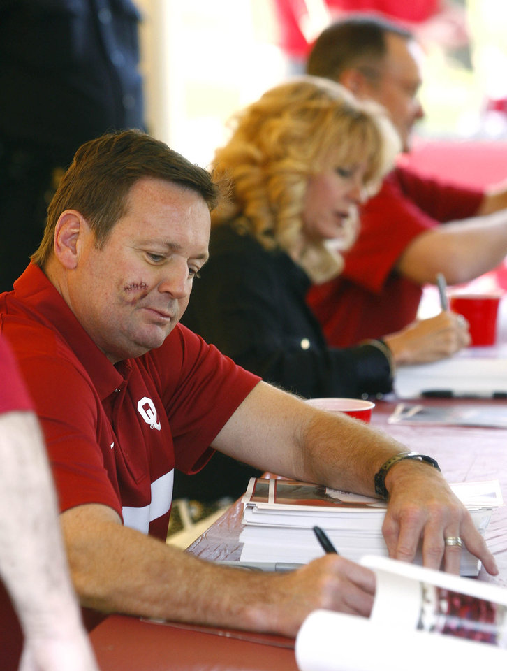 Photo - OU coaches Bob Stoops (left), Sherri Coale and Lon Kruger (top right) sign autographs during the Sooner Caravan at OU-Tulsa on Monday, May 6, 2013. MATT BARNARD/Tulsa World ORG XMIT: DTI1305062004281125