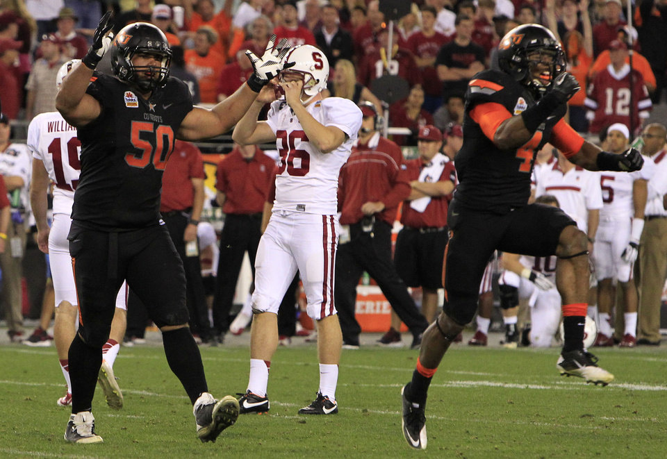 Photo - A dejected Stanford's Daniel Zychlinski (36) grabs his helmet as Oklahoma State's Jamie Blatnick (50) and Justin Gilbert (4) celebrate a missed Stanford field goal attempt during overtime in the Fiesta Bowl NCAA college football game Monday, Jan. 2, 2012, in Glendale, Ariz.  Oklahoma State defeated Stanford 41-38 in overtime.(AP Photo/Ross D. Franklin) ORG XMIT: PNP158
