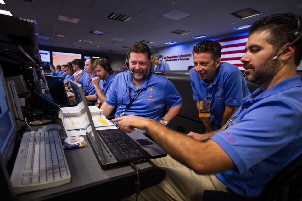In this photo released by NASA's JPL, Mars Science Laboratory (MSL) team members talk in the MSL Mission Support Area at the Jet Propulsion Laboratory ahead of the planned landing of the Curiosity rover on Mars, Sunday, Aug. 5, 2012 in Pasadena, Calif. The MSL Rover named Curiosity was designed to assess whether Mars ever had an environment able to support small life forms called microbes. Curiosity is due to land on Mars at 10:31 p.m. PDT on Aug. 5, 2012 (1:31 a.m. EDT on Aug. 6, 2012) (AP Photo/NASA, Bill Ingalls)