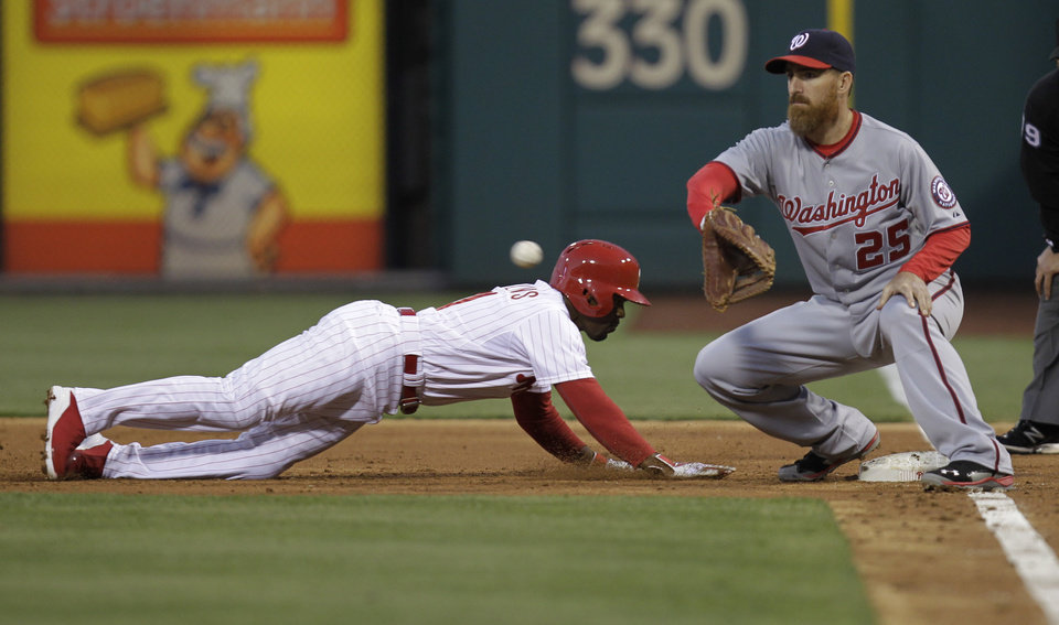 Photo - Philadelphia Phillies' Jimmy Rollins is safe on a pickoff-attempt at first before Washington Nationals' Adam LaRoche can make the tag in the third inning of a baseball game on Friday, May 2, 2014, in Philadelphia. (AP Photo/Laurence Kesterson)