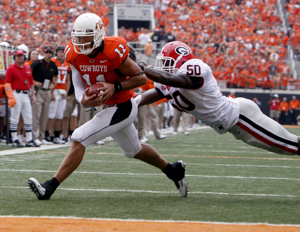 Photo - OSU's Zac Robinson (11) rushes as Georgia's Darryl Gamble (50) tries to bring him down during the college football game between OSU and the University of Georgia at Boone Pickens Stadium on the campus of Oklahoma State University in Stillwater Saturday, Sept. 5, 2009. Photo by Sarah Phipps, The Oklahoman.     ORG XMIT: KOD
