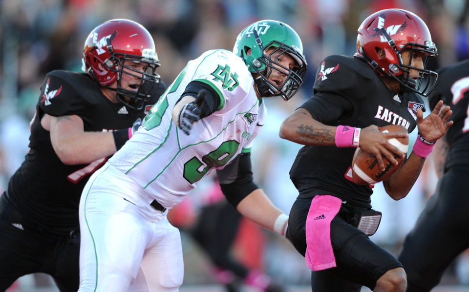 Photo -   Eastern Washington quarterback Vernon Adams, right, runs the ball as North Dakota's Ross Brenneman (98) closes in for a sack during the first half of an NCAA college football game on Saturday, Oct. 6, 2012, at Roos Field in Cheney, Wash. (AP Photo/The Spokesman-Review, Tyler Tjomsland) COEUR D'ALENE PRESS OUT