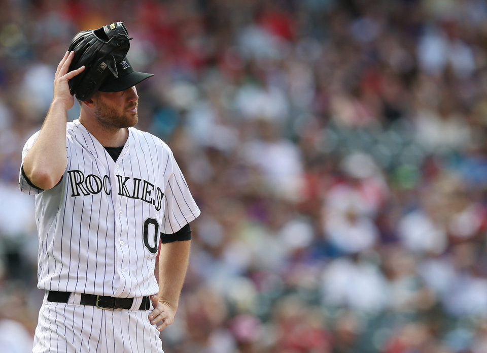Photo - Colorado Rockies relief pitcher Adam Ottavino puts his glove on his head after retiring the St. Louis Cardinals but giving up two runs in the eighth inning of the Cardinals' 9-6 victory in a baseball game in Denver on Wednesday, June 25, 2014. (AP Photo/David Zalubowski)