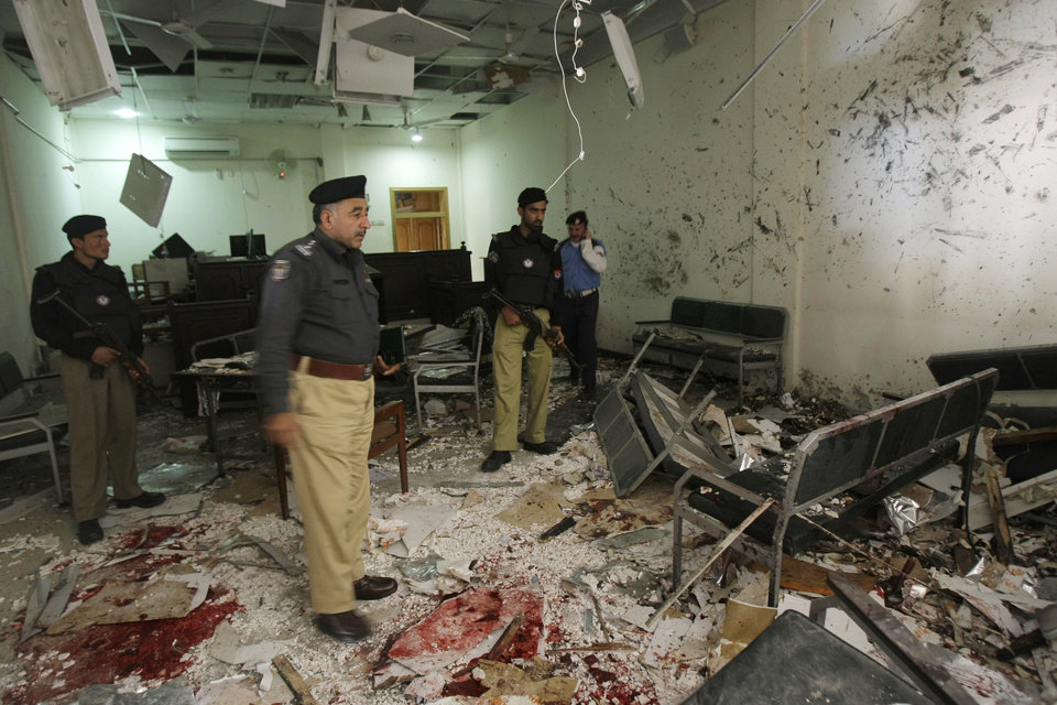 Pakistani police officers examine the site of suicide bombing inside a court room in Peshawar, Pakistan, Monday, March 18, 2013. A pair of suicide bombers attacked a court complex in the northwestern Pakistani city of Peshawar on Monday, killing at least three people and wounding over two dozen, police said. (AP Photo/Mohammad Sajjad)