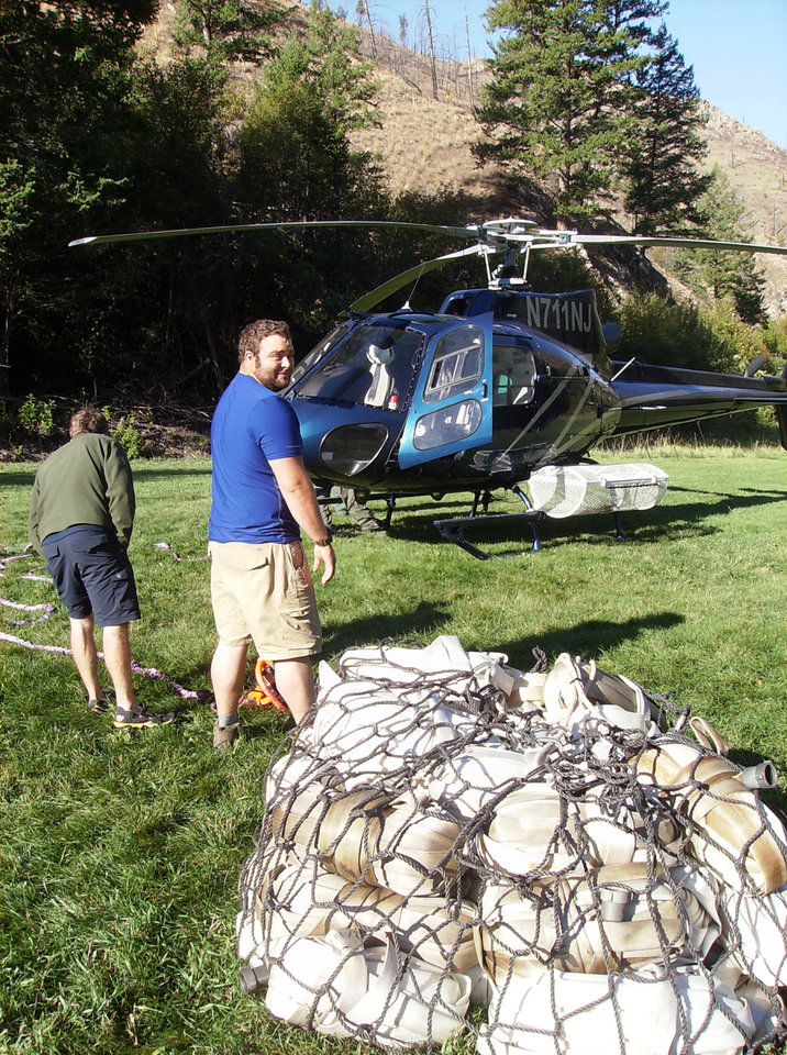 Photo - In this Fall 2013 photo provided by the University of Idaho, student Todd Kriner of Delaware Valley College helps unload supplies from a helicopter at the Taylor Wilderness Research Station operated by the University of Idaho in the Frank Church-River Of No Return Wilderness, Idaho. Kriner is one of the university's first Semester in the Wild Class students. (AP Photo/University of Idaho)