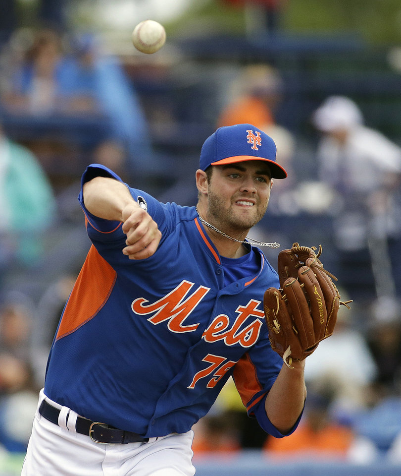Photo - New York Mets starting pitcher Cory Mazzoni throws to first base in pickoff attempt of Washington Nationals' Wilson Ramos in the second inning of an exhibition spring training baseball game, Thursday, March 27, 2014, in Port St. Lucie, Fla. (AP Photo/David Goldman)