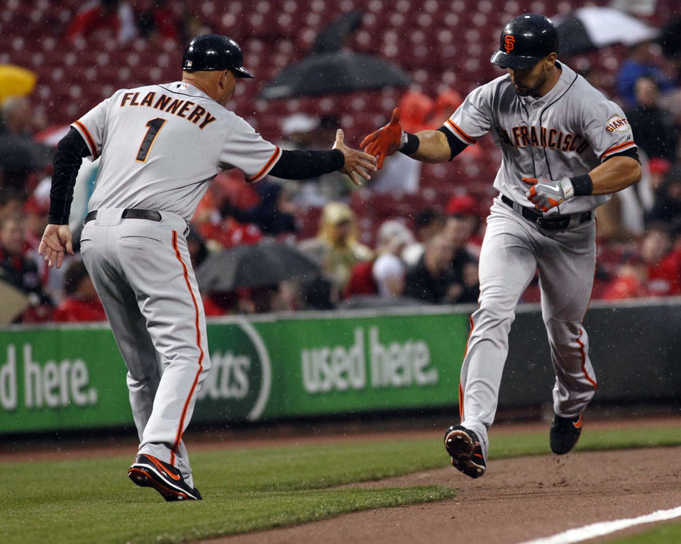San Francisco Giants third base coach Tim Flannery, left, greets Giants' Angel Pagan who hit a one-run home run in the third inning of a baseball game against the Cincinnati Reds, Wednesday, April 25, 2012, in Cincinnati. (AP Photo/Ernest Coleman)