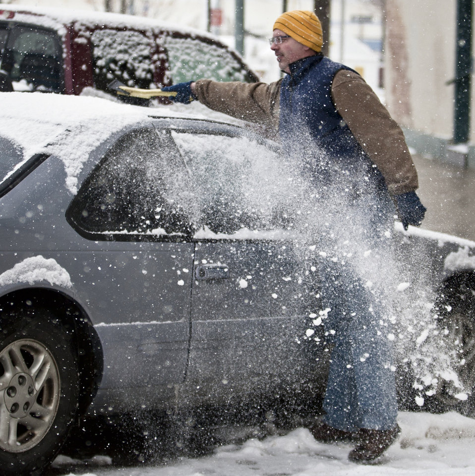 Photo - Laramie resident John Waggener brushes the snow from the roof of his car after enjoying dinner at a downtown restaurant in Laramie, Wyo., Tuesday, April 9, 2013. (AP Photo/Laramie Boomerang, Jeremy Martin)