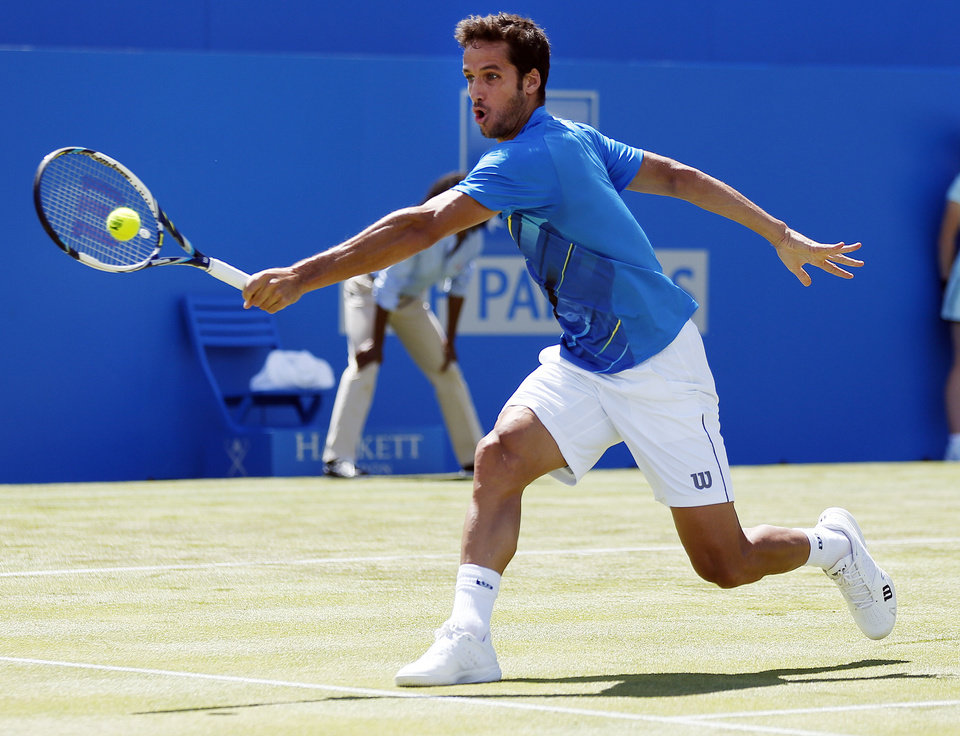 Photo - Spain's Feliciano Lopez in action against Serbia's Dusan Lajovic at the Queen's Club grass-court tournament in  London Tuesday June 10, 2014. (AP PhotoJonathan Brady/PA) UNITED KINGDOM OUT