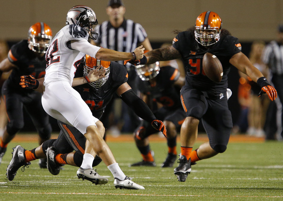 Photo - Texas Tech's Taylor Symmank (42) tries to pass the ball after dropping the ball on a punt as Oklahoma State's James Castleman (91) and Ofa Hautau (98) during a college football game between the Oklahoma State Cowboys (OSU) and the Texas Tech Red Raiders at Boone Pickens Stadium in Stillwater, Okla., Thursday, Sept. 25, 2014. Photo by Bryan Terry, The Oklahoman