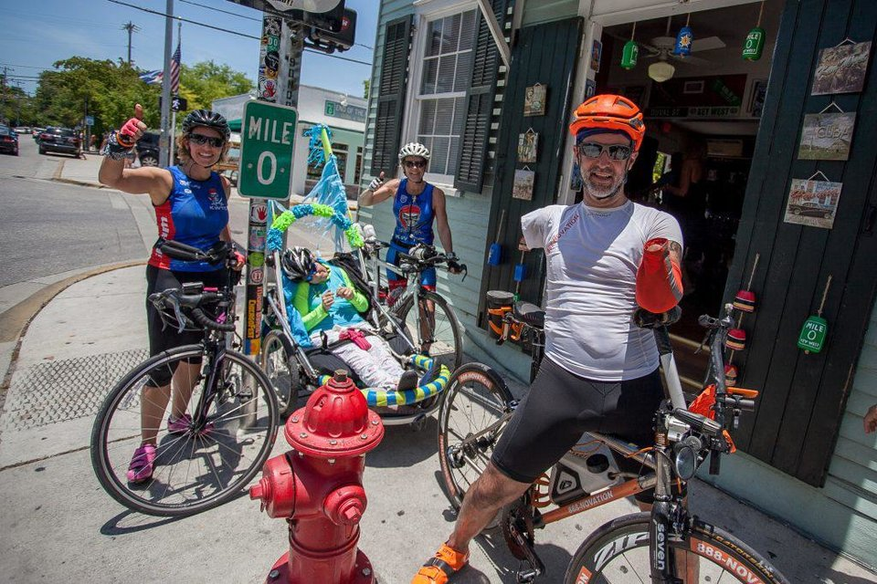 Photo - Double amputee Hector Picard and Kelly Gruson, second from left , who is quadriplegic, completed a 50-mile race Wednesday, assisted by members of the Key West Triathlon Club. Photo credit: Julio Mendez.