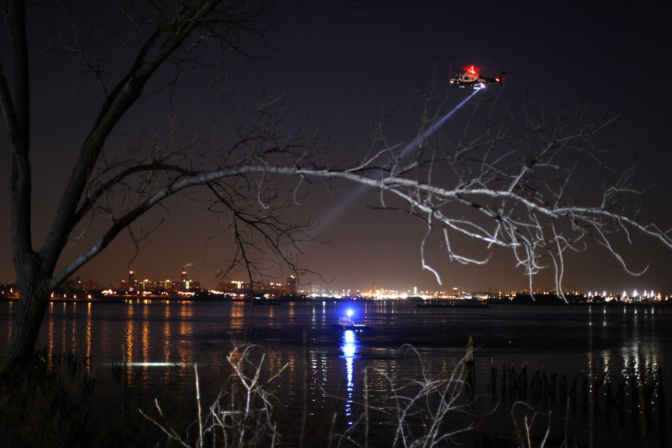 Photo - Police continue the search for human remains after an arm and legs were discovered along a rocky shoreline in the Queens borough of New York, Friday, Jan. 17, 2014. (AP Photo/Jason DeCrow)