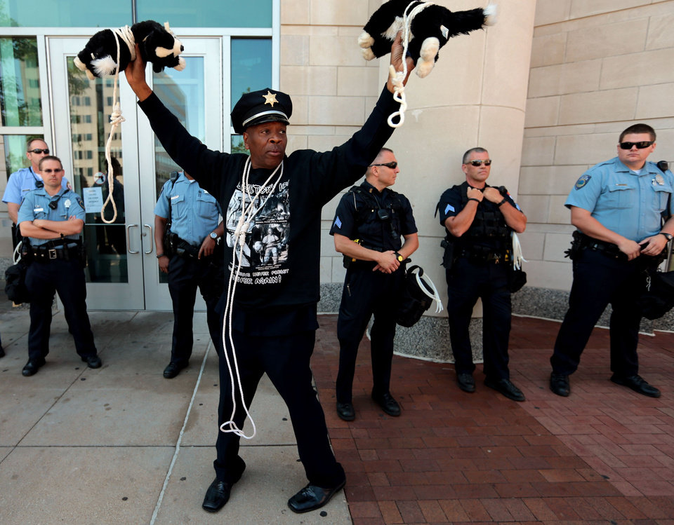 Photo - Activist Anthony Shahid holds up two stuffed dogs which he wore around his neck during a rally across the Justice Center, Tuesday, Aug. 12, 2014, in Clayton, Mo., demanding justice for Michael Brown Jr. who was fatally shot by a Ferguson police officer last Saturday. Shahid said