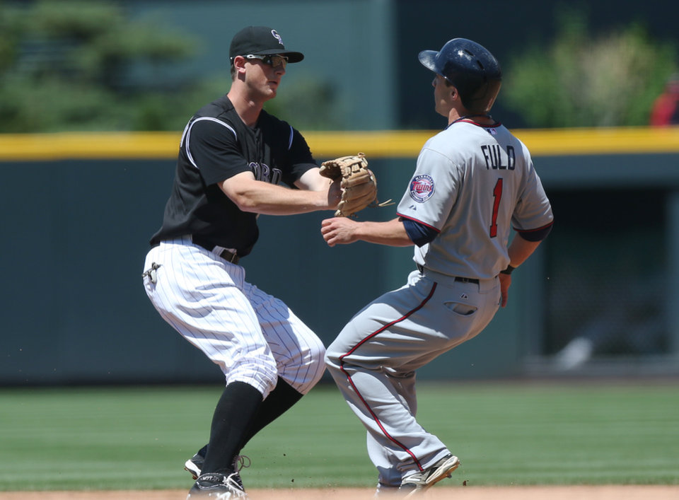 Photo - Colorado Rockies second baseman DJ LeMahieu, left, tags out Minnesota Twins' Sam Fuld as he tries to advance from first to second base in the first inning of an interleague baseball game in Denver on Sunday, July 13, 2014. (AP Photo/David Zalubowski)