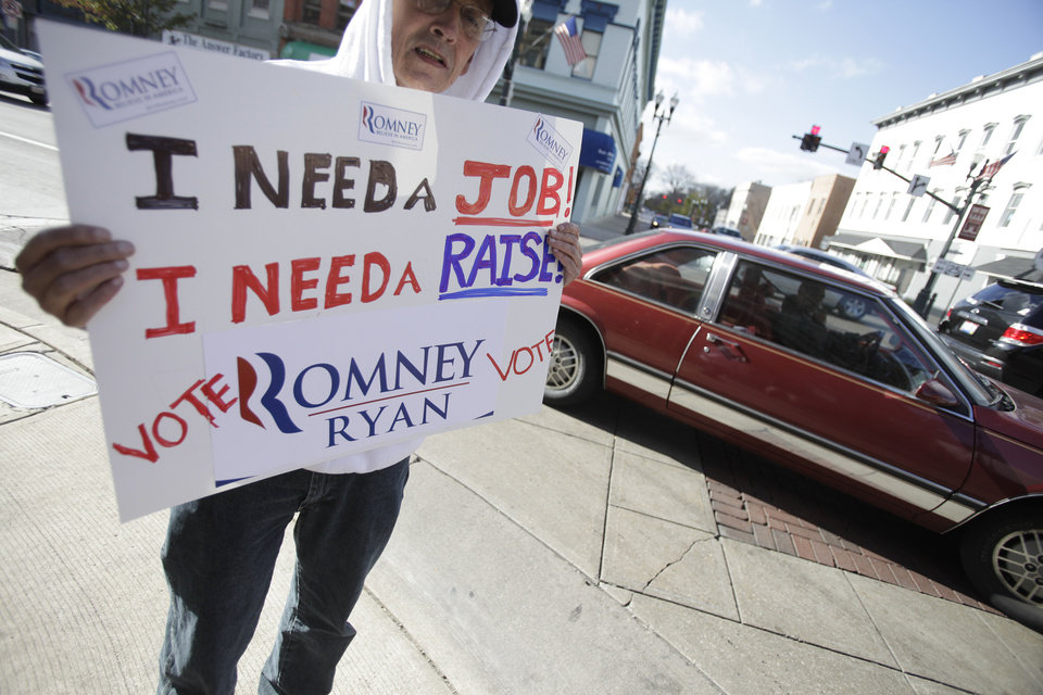 Photo -   John DeNoyelles, from Flint, Texas, who said he is in Ohio trying to network to find a job, holds a sign in support of Mitt Romney along Main Street in Bowling Green, Ohio Monday Nov. 5, 2012. (AP Photo/J.D. Pooley)