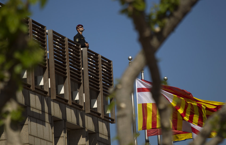 Photo -   A police officer stands guard at the hotel where the meeting of the European Central Bank is taking place in Barcelona, Spain, Thursday, May 3, 2012. European stocks pushed ahead Thursday after cash-strapped Spain got through another set of bond auctions unscathed and ahead of the latest policy statement from the European Central Bank's president Mario Draghi. (AP Photo/Emilio Morenatti)