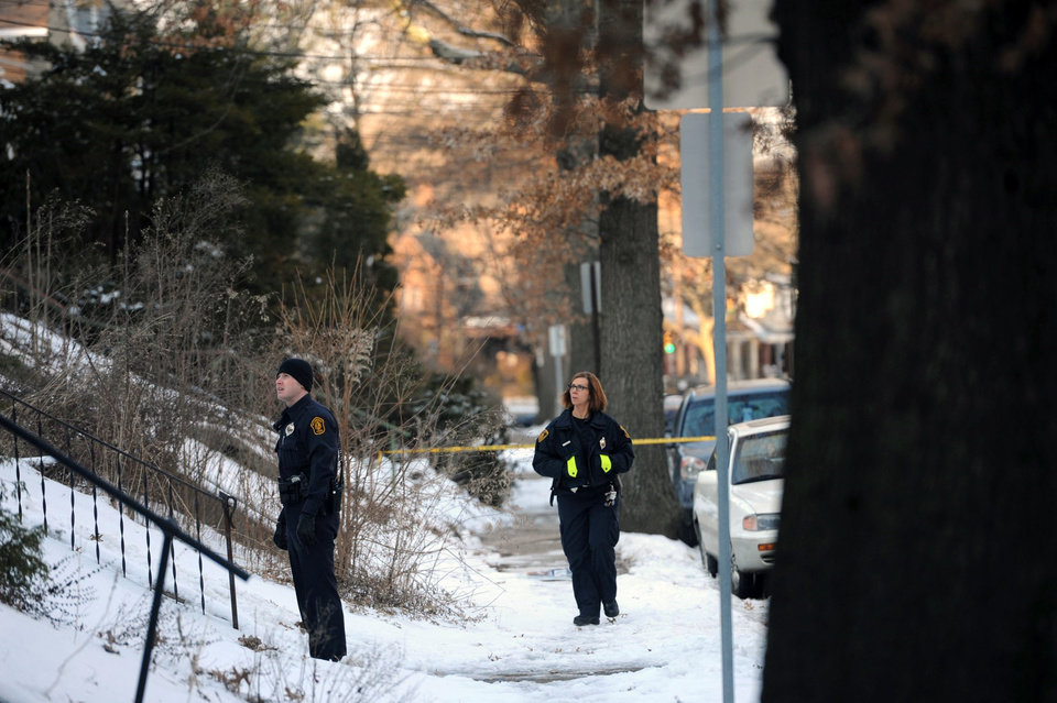 Photo - In this Feb. 7, 2014 photo, police investigate the scene were the bodies of sisters Susan Wolfe and Sarah Wolfe were found in the basement of their home in Pittsburgh. The two were sisters of an Iowa state representative, Mary Wolfe. Police said that they are investigating the case as a double homicide. (AP Photo/Pittsburgh Post-Gazette, Rebecca Droke)