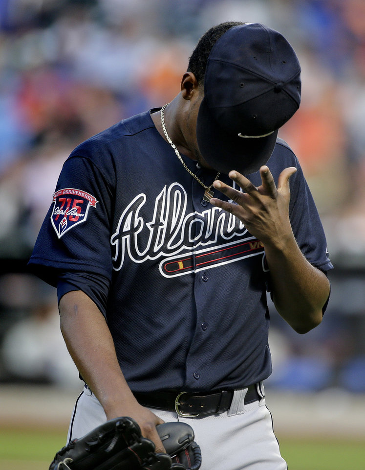 Photo - Atlanta Braves pitcher Julio Teheran (49) flips his cap off his head as he walks off the field after giving up three runs to the New York Mets in the second inning of a baseball game, Tuesday, July 8, 2014, in New York. (AP Photo/Julie Jacobson)