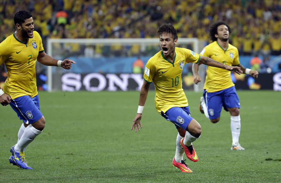 Photo - Brazil's Neymar, centre, celebrates after scoring his sides first goal during the group A World Cup soccer match between Brazil and Croatia, the opening game of the tournament, in the Itaquerao Stadium in Sao Paulo, Brazil, Thursday, June 12, 2014.  (AP Photo/Felipe Dana)
