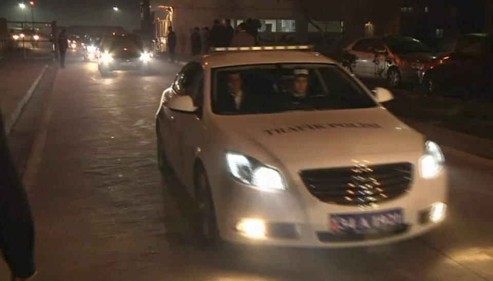 Photo - In this image from TV, a police vehicle carrying Huseyin Avni Mutlu, the Istanbul governor, leads a convoy of cars believed to be carrying released passengers who were held hostage aboard a plane, Friday Feb. 7, 2014. All 110 passengers aboard the plane were evacuated