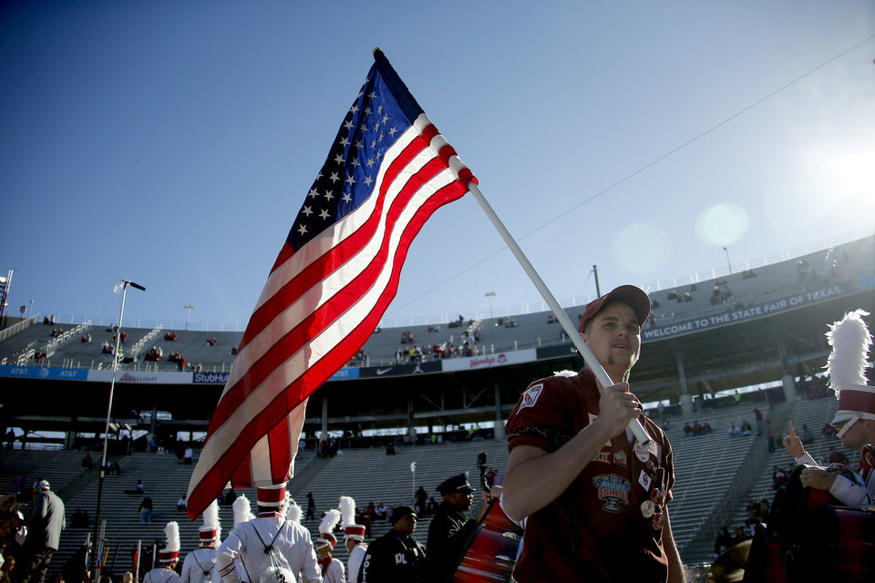 Photo - A RUF/NEK holds an American flag before the Red River Showdown college football game between the University of Oklahoma Sooners (OU) and the Texas Longhorns (UT) at Cotton Bowl Stadium in Dallas, Saturday, Oct. 12, 2019. [Bryan Terry/The Oklahoman]