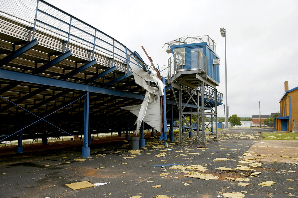 Photo - Pieces from the roof of a gymnasium at Choctaw Middle School hang from the bleachers at the school's football field after high winds from a storm caused damage in Choctaw, Okla.,, Tuesday, Aug. 27, 2019. [Bryan Terry/The Oklahoman]
