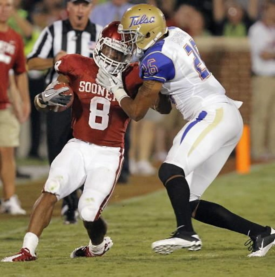 Photo - Tulsa's Dexter McCoil (26) tries to stop Oklahoma's Dominique Whaley (8) during the college football game between the University of Oklahoma Sooners ( OU) and the Tulsa University Hurricanes (TU) at the Gaylord Family-Memorial Stadium on Saturday, Sept. 3, 2011, in Norman, Okla. Photo by Chris Landsberger, The Oklahoman ORG XMIT: KOD