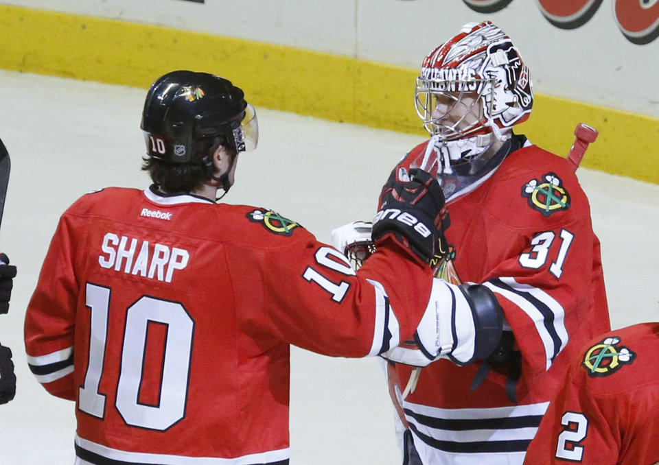 Chicago Blackhawks left wing Patrick Sharp (10) celebrates with goalie Antti Raanta the Blackhawks' 7-2 win over the Philadelphia Flyers after an NHL hockey game Wednesday, Dec. 11, 2013, in Chicago. (AP Photo/Charles Rex Arbogast)