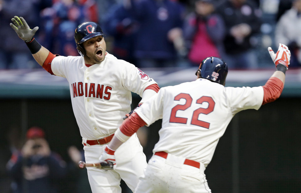 Photo - Cleveland Indians' Nick Swisher, left, celebrates with teammate Jason Kipnis after hitting a two-run home run off Minnesota Twins starting pitcher Mike Pelfrey in the sixth inning of a baseball game on Friday, April 4, 2014, in Cleveland. Lonnie Chisenhall also scored. (AP Photo/Mark Duncan)