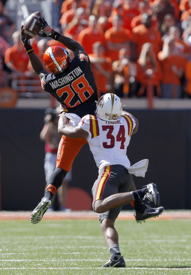 Photo - Oklahoma State's James Washington (28) makes a catch in front of Iowa State's Nigel Tribune (34) during a college football game between the Oklahoma State University Cowboys (OSU) and the Iowa State University at Boone Pickens Stadium in Stillwater, Okla., Saturday, Oct. 8, 2016. Photo by Sarah Phipps, The Oklahoman