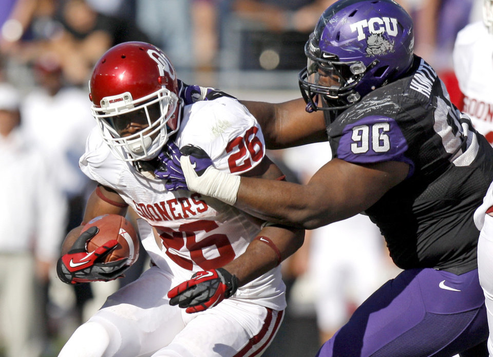 Photo - Oklahoma's Damien Williams (26) tries to get past TCU's Chucky Hunter (96) during a college football game between the University of Oklahoma Sooners (OU) and the Texas Christian University Horned Frogs (TCU) at Amon G. Carter Stadium in Fort Worth, Texas, Saturday, Dec. 1, 2012. Oklahoma won 24-17. Photo by Bryan Terry, The Oklahoman