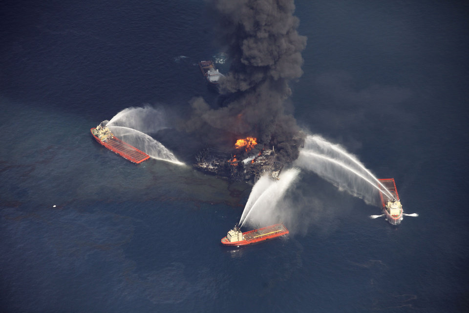 Photo - FILE - In this aerial file photo madeWednesday, April 21, 2010 in the Gulf of Mexico, more than 50 miles southeast of Venice on Louisiana's tip, an oil slick is seen as the Deepwater Horizon oil rig burns. Nearly three years after the deadly rig explosion in the Gulf of Mexico triggered the nation's worst offshore oil spill, a federal judge in New Orleans is set to preside over a high-stakes trial for the raft of litigation spawned by the disaster on Monday Feb. 25, 2013. (AP Photo/Gerald Herbert, file)