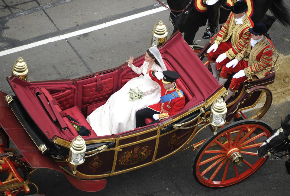 Photo - Britain's Prince William and Kate, the Duchess of Cambridge, wave as they travel in the 1902 State Landau carriage along the processional route to Buckingham Palace, London, Friday April 29, 2011. (AP Photo/Damien Meyer, Pool)  ORG XMIT: RWDJ121