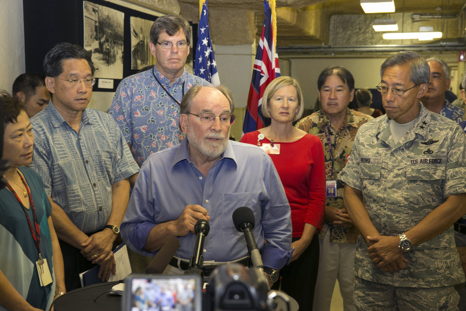 Photo - While surrounded by state and local officials, Hawaii Gov. Neil Abercrombie speaks at a news conference at the Hawaii Emergency Management Agency in Diamond Head, Thursday, Aug. 7, 2014, in Honolulu.  Hawaii is bracing for two back to back hurricanes, Iselle and Julio, which are on course to hit the Hawaiian Islands.  (AP Photo/Marco Garcia)