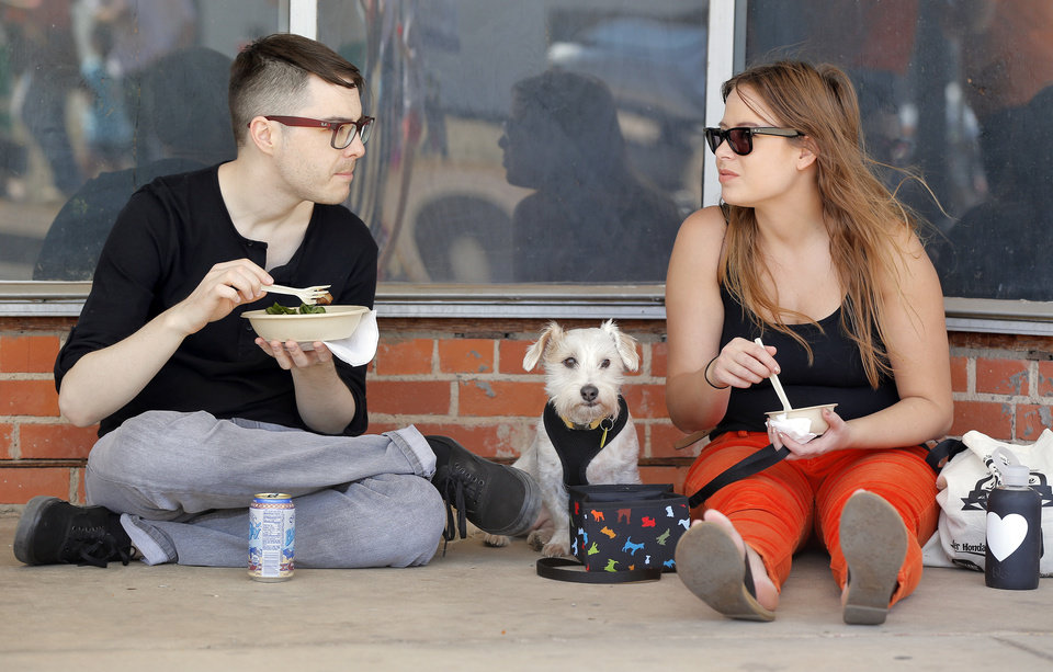 Photo - Benji Dodson, left, and his wife, Danielle Dodson, eat in the shade with their dog, Cloud, during the Open Streets OKC event.  Photos by Nate Billings, The Oklahoman  NATE BILLINGS