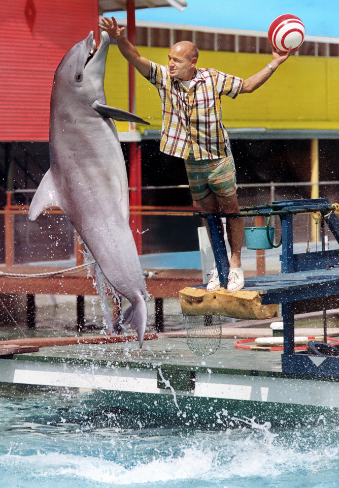 Photo - Bob Jenni, director of the Springlake Sea Aquarium, does a little poolside training with Konki the porpoise at Springlake Amusement Park.    Staff  COLOR photo taken by Al McLaughlin; photo ran on the cover of the Showcase Magazine in the 6/8/1969 (Sunday) Daily Oklahoman.