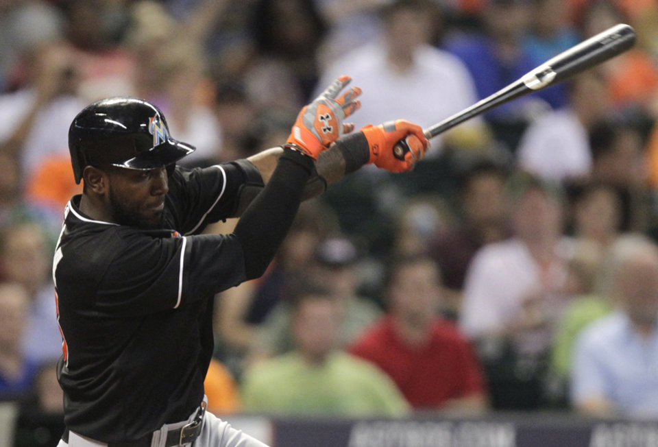 Photo - Miami Marlins' Marcell Ozuna singles to left field during the fifth inning of a baseball game against the Houston Astros, Friday, July 25, 2014, in Houston. (AP Photo/Patric Schneider)