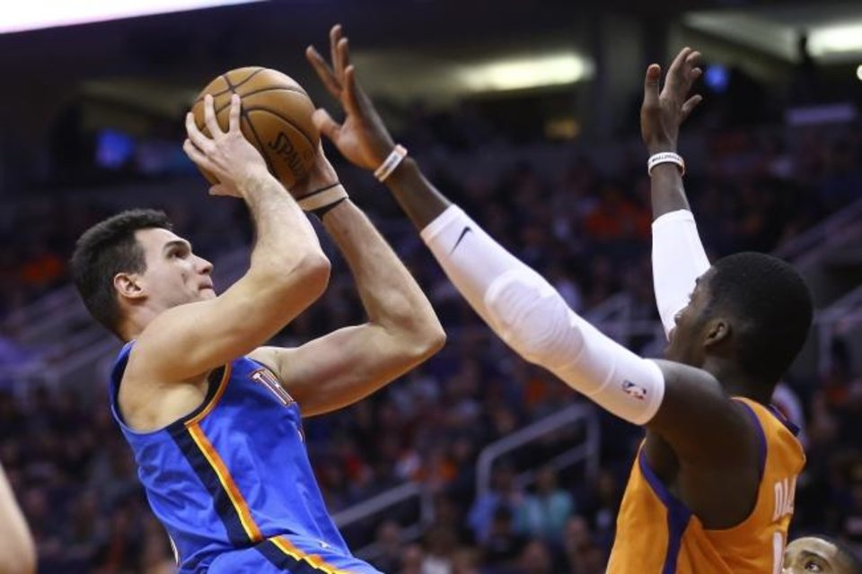 Photo -  Thunder forward Danilo Gallinari, left, shoots over Suns forward Cheick Diallo during the first half Friday. [AP Photo/Ross D. Franklin]