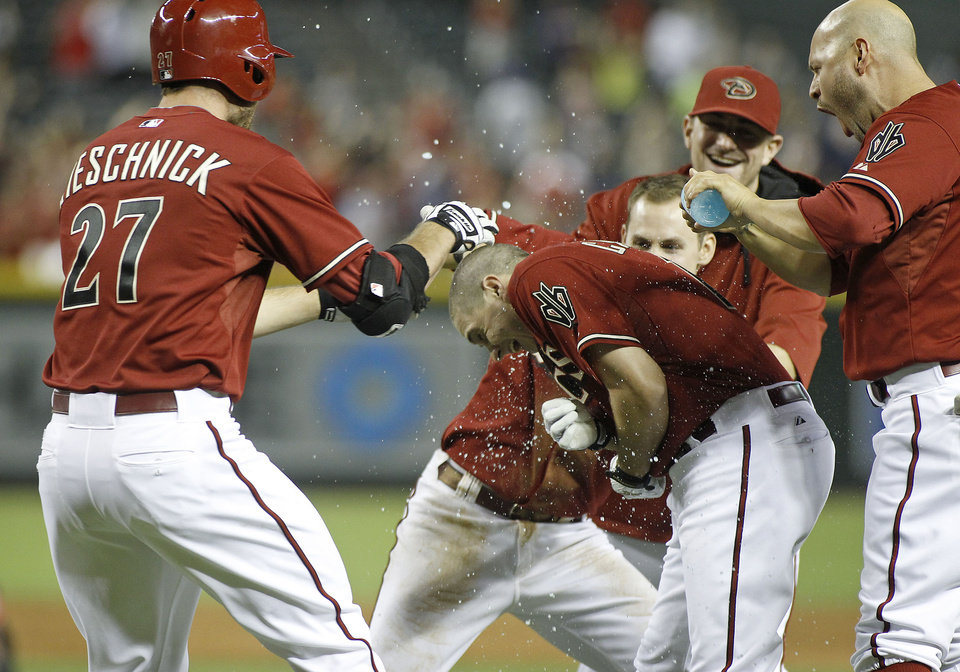 Photo - Arizona Diamondbacks' Tony Campana, front center, is dowsed with water by teammates Cody Ross, right, Chris Owings, no hat, Daniel Hudson, background, and Roger Kieschnick (27) after his game winning RBI single against the Milwaukee Brewers during the ninth inning of a baseball game on Wednesday, June 18, 2014, in Phoenix. The Diamondbacks defeated the Brewers 4-3. (AP Photo/Ralph Freso)