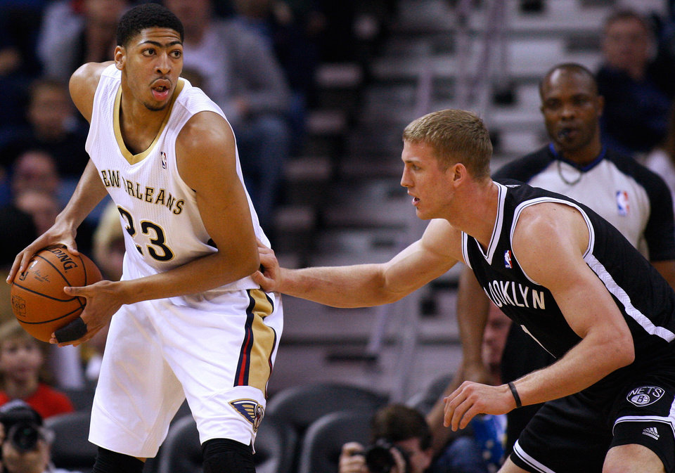 Photo - New Orleans Pelicans forward Anthony Davis (23) drives against Brooklyn Nets forward Mason Plumlee, right, during the first half of an NBA basketball game in New Orleans, Monday, March 24, 2014. (AP Photo/Jonathan Bachman)