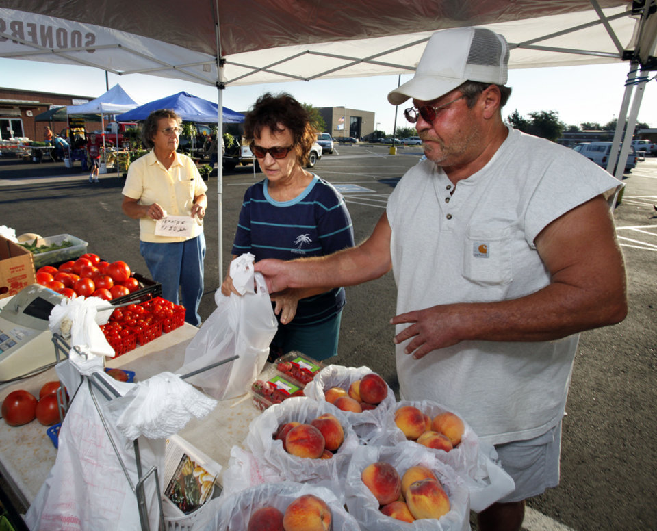 Photo - Terry Nixon, with Elam Produce of Purcell, helps Rita Doussett, of Norman, at the Norman Farmers Market last fall.Photo by Steve Sisney, The Oklahoman Archives