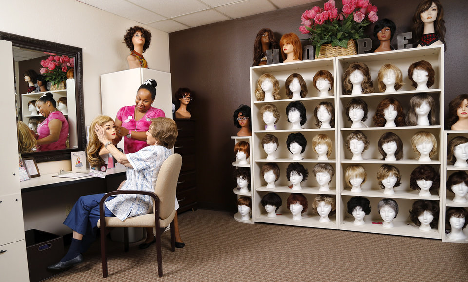Photo -  Nicole Danley, left, looks at wig selections with Frieda Watts in the wig room at the American Cancer Society in Oklahoma City. [BY JIM BECKEL, THE OKLAHOMAN]