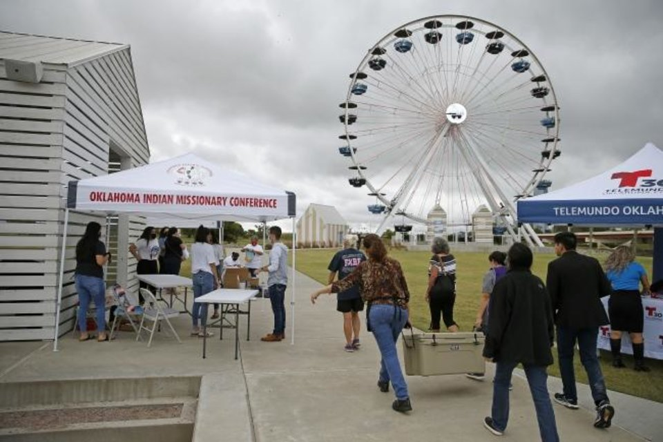 Photo -  People carry supplies as they set up booths Tuesday during a voter registration drive at the Wheeler Ferris wheel. [Bryan Terry/The Oklahoman]