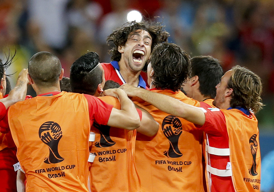 Photo - Chile's Jorge Valdivia, top center, celebrates after scoring his side's second goal during the group B World Cup soccer match between Chile and Australia in the Arena Pantanal in Cuiaba, Brazil, Friday, June 13, 2014.   (AP Photo/Frank Augstein)